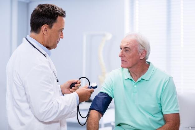 Medico che controlla la pressione sanguigna di un paziente