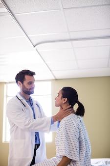 Medico che esamina il collo dei pazienti in ospedale