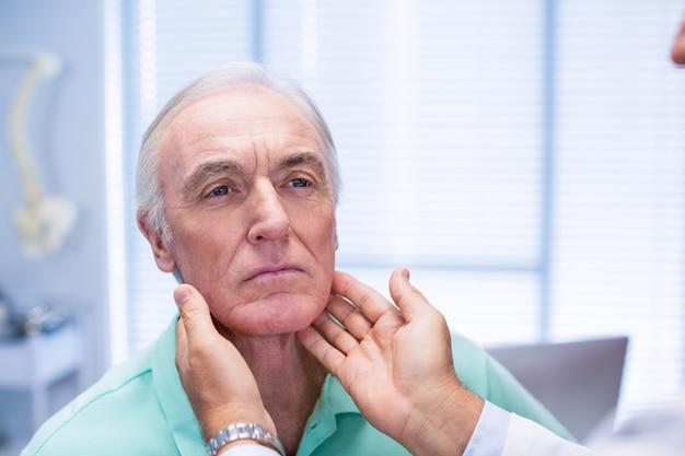Medico che esamina il collo dei pazienti senior