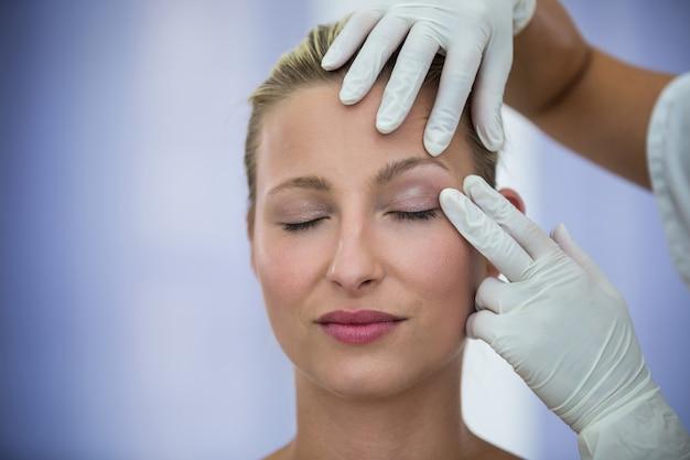 Medico che esamina il fronte femminile dei pazienti dal trattamento cosmetico