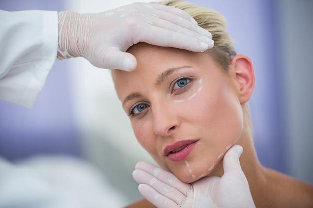Medico che esamina il fronte femminile dei pazienti per il trattamento cosmetico