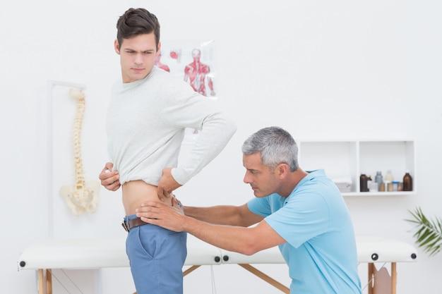 Medico che esamina il suo paziente indietro in studio medico