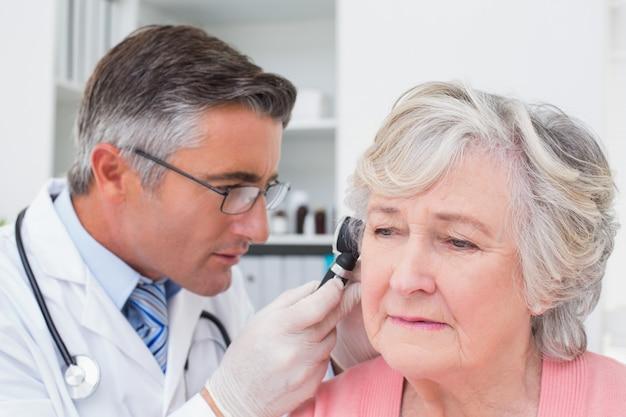 Medico che esamina l'orecchio dei pazienti con l'otoscopio
