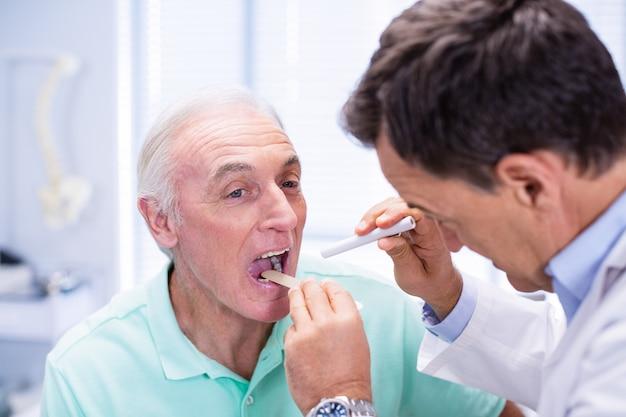 Medico che esamina la bocca senior dei pazienti