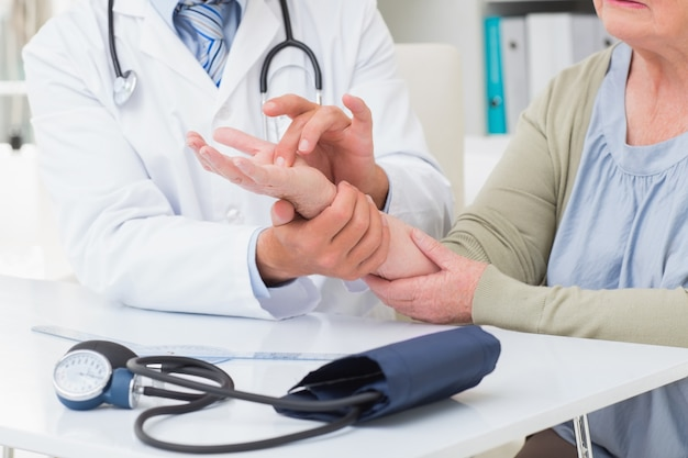 Medico che esamina la mano dei pazienti al tavolo