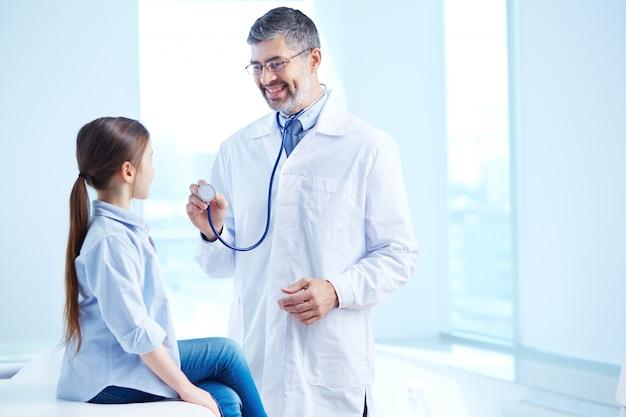 Medico che esamina la sua giovane paziente