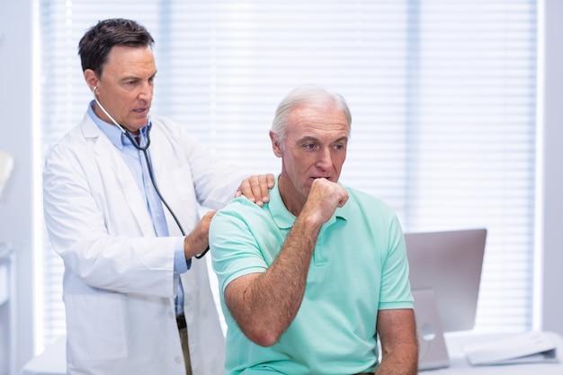 Medico che esamina paziente senior