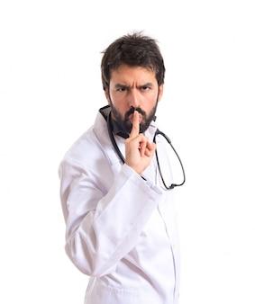 Medico che fa gesto di silenzio su sfondo bianco isolato