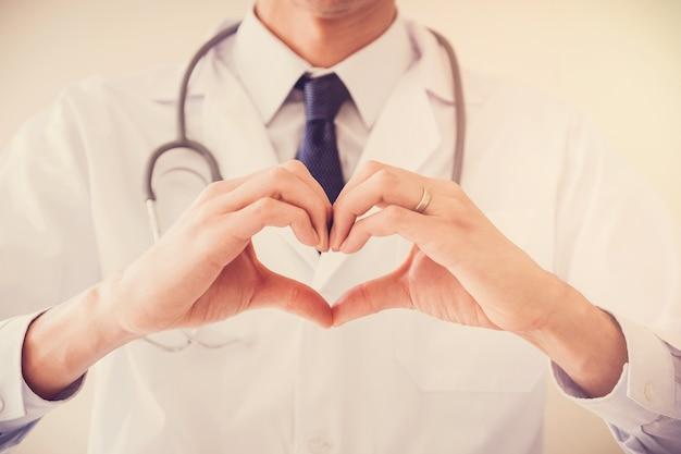 Medico che fa le sue mani nella forma del cuore, concetto di assicurazione malattia del cuore