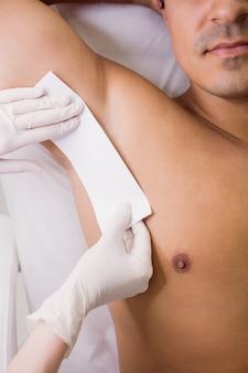Medico che incera la pelle paziente maschio in clinica