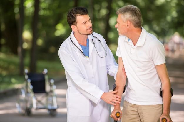 Medico che incoraggia il suo paziente a camminare con le stampelle.
