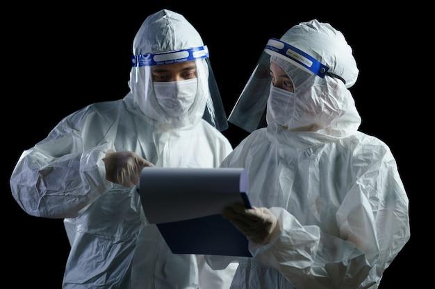 Medico che indossa dpi e visiera in cerca di un rapporto di laboratorio sul virus corona / covid-19.