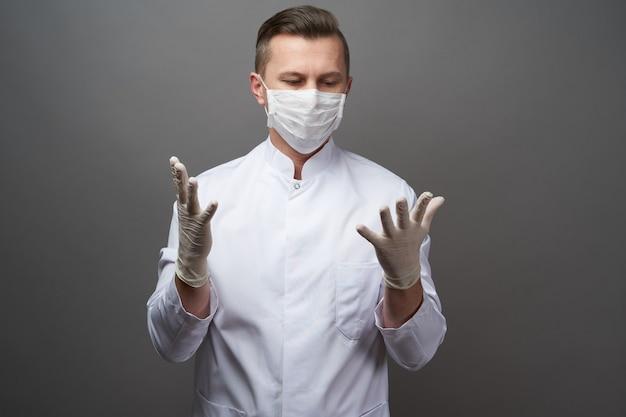 Medico che indossa guanti protettivi in lattice e maschera facciale