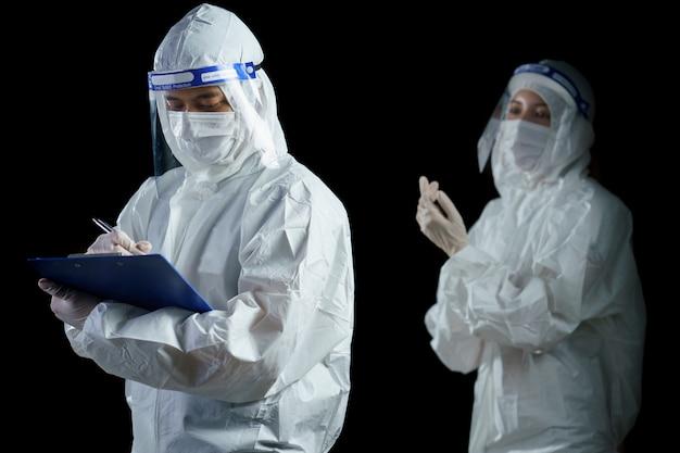 Medico che indossa ppe e la scrittura dello scudo facciale per il rapporto di laboratorio sul virus corona / covid-19.