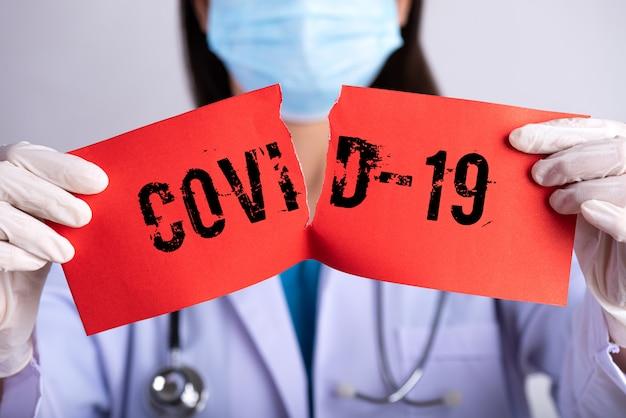 Medico che indossa una maschera chirurgica, stetoscopio e in possesso di carta strappata rossa con testo covid-19