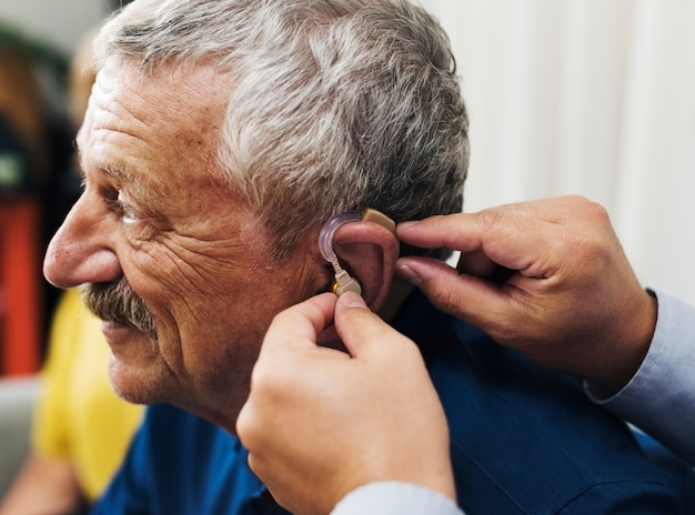 Medico che inserisce l'apparecchio acustico all'orecchio del paziente