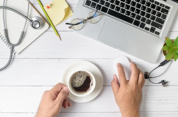 Medico che lavora con il computer portatile e bere un caffè