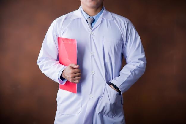 Medico che lavora in possesso di un blocco per appunti
