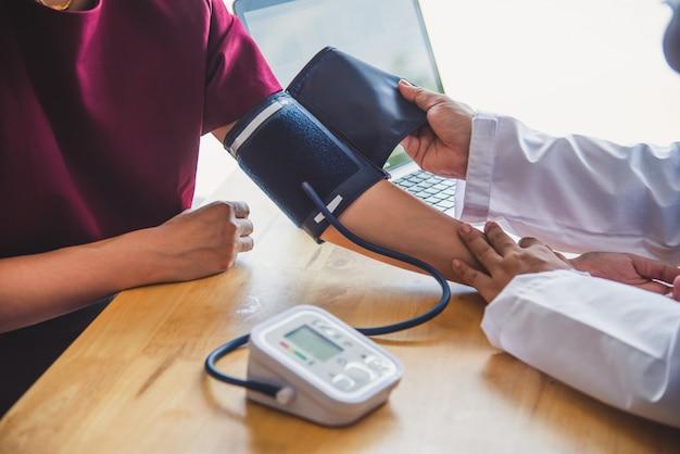 Medico che misura la pressione sanguigna dal suo paziente