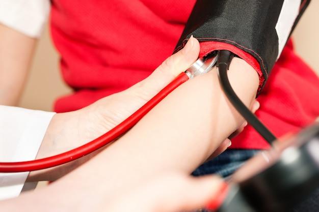 Medico che misura la pressione sanguigna del bambino