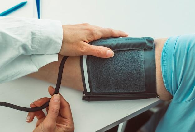 Medico che misura la pressione sanguigna.
