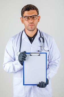 Medico che mostra appunti in bianco in abito bianco medico