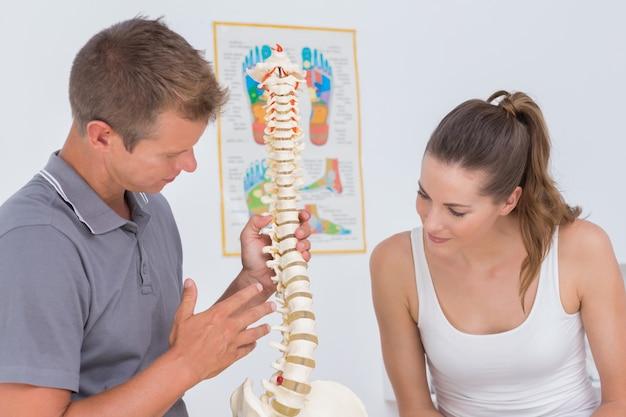 Medico che mostra la spina dorsale anatomica al suo paziente