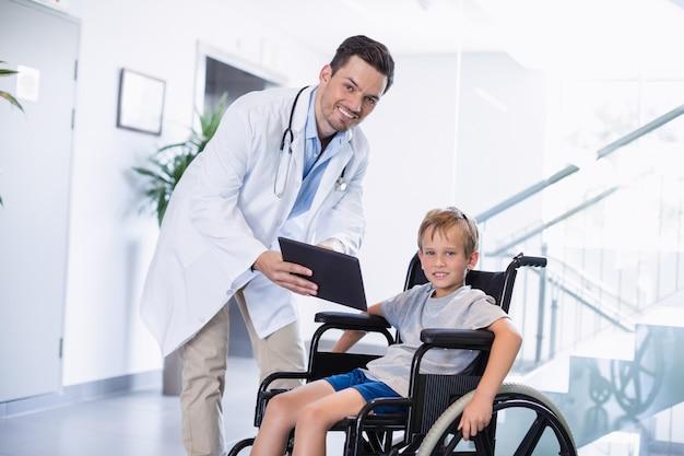 Medico che mostra la tavoletta digitale per disabilitare il ragazzo