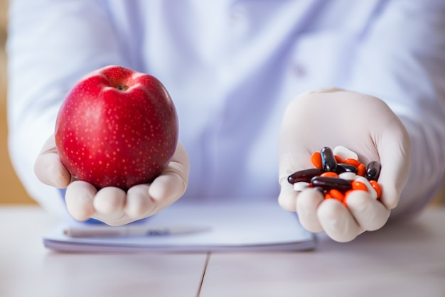 Medico che offre la scelta tra sano e vitamine