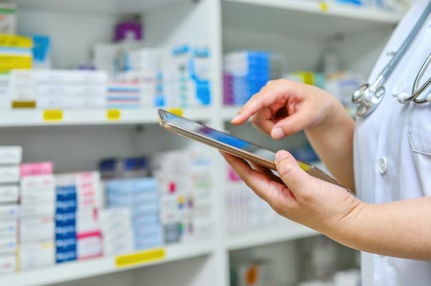 Medico che per mezzo della compressa del computer per la barra di ricerca su esposizione negli scaffali della farmacia della farmacia concetto medico online.