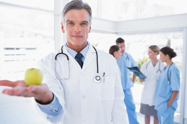 Medico che presenta una mela in mano