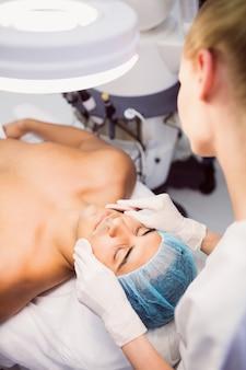 Medico che pulisce il viso del paziente con una spugna per il viso