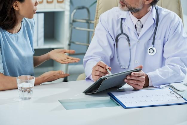 Medico che punta allo schermo della tavoletta digitale mentre spiega qualcosa al paziente
