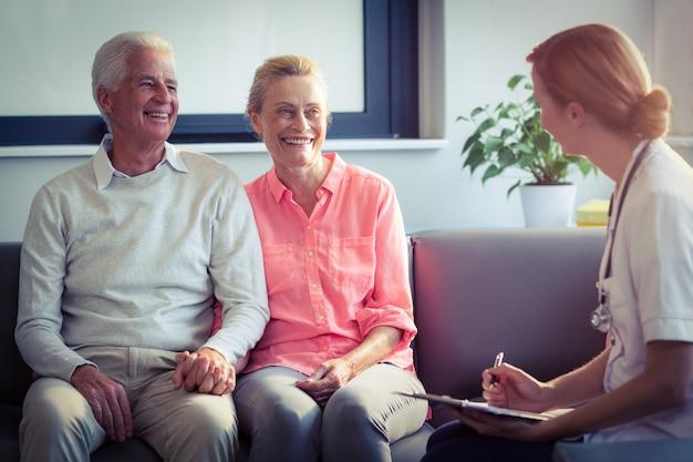 Medico che scrive rapporto medico delle coppie senior