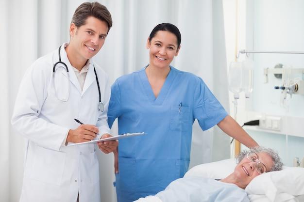 Medico che sorride mentre si tiene una lavagna per appunti