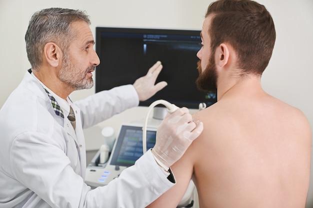 Medico che spiega alla scansione paziente della sua spalla.