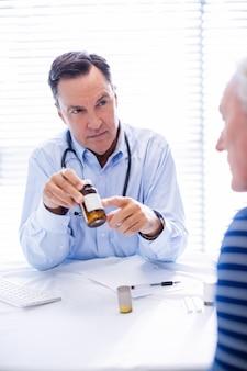 Medico che spiega medicina al paziente senior