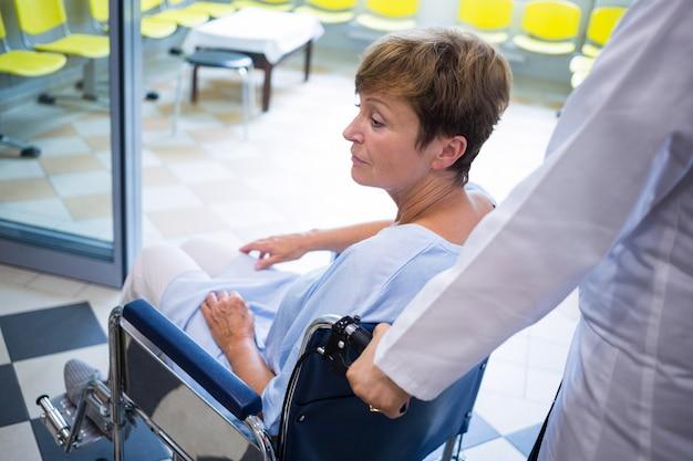 Medico che spinge paziente senior sulla sedia a rotelle