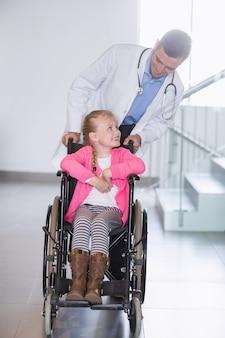 Medico che spinge ragazza in sedia a rotelle