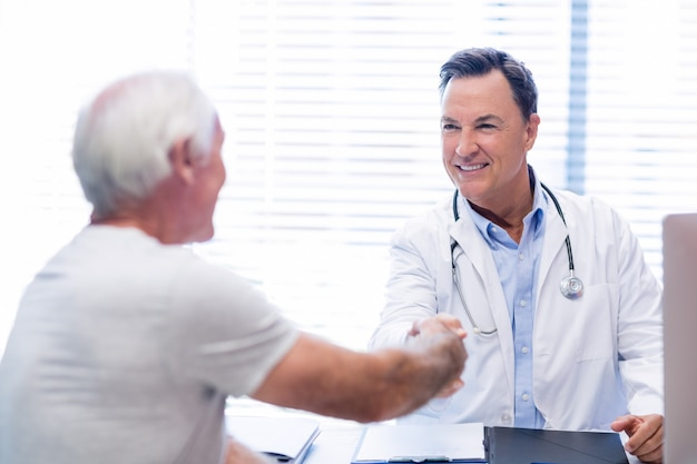 Medico che stringe la mano con l'uomo senior