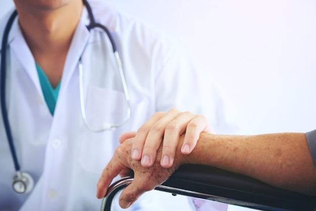 Medico che tiene la mano del paziente anziano in una sedia a rotelle