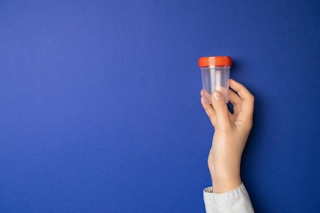 Medico che tiene la tazza del campione. test medico per l'urina in ospedale.