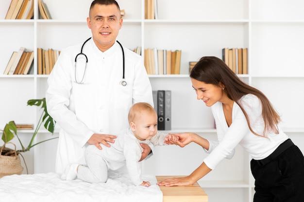 Medico che tiene piccolo bambino e guardando fotografo