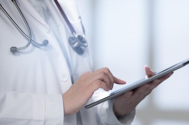 Medico che utilizza compressa astuta per lavoro nell'ospedale