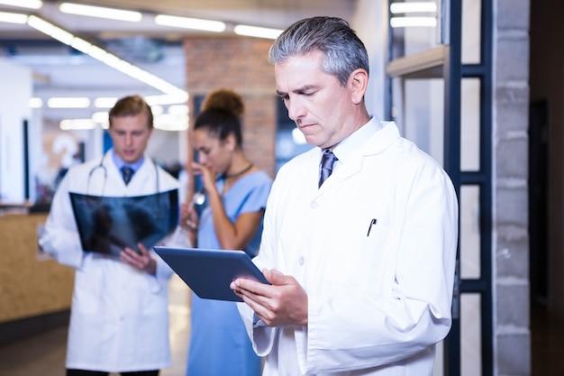 Medico che utilizza compressa digitale nell'ospedale e colleghi che stanno dietro e che discutono