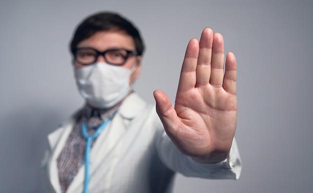 Medico cinese asiatico in una mascherina medica e vetri che mostrano un fanale di arresto d'avvertimento con la sua mano.