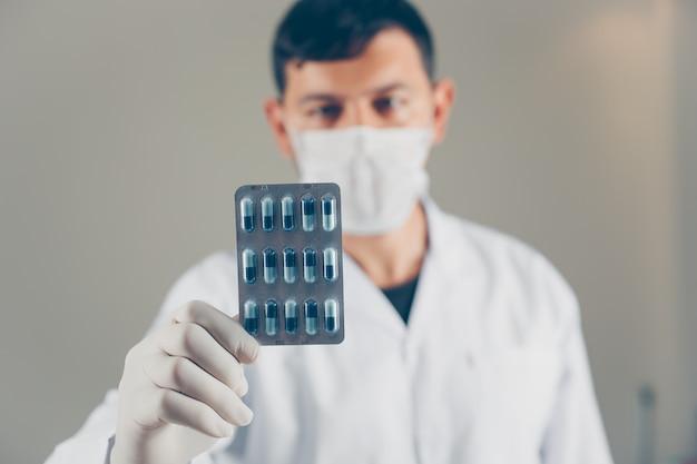 Medico con i guanti e la maschera che tengono una vista laterale del pacchetto della pillola