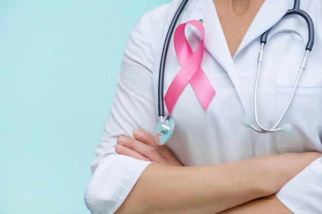 Medico con le braccia conserte e uno stetoscopio sul collo, mostra un primo piano di nastro rosa in uniforme