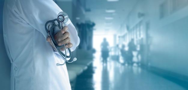 Medico con lo stetoscopio a disposizione sul fondo dell'ospedale