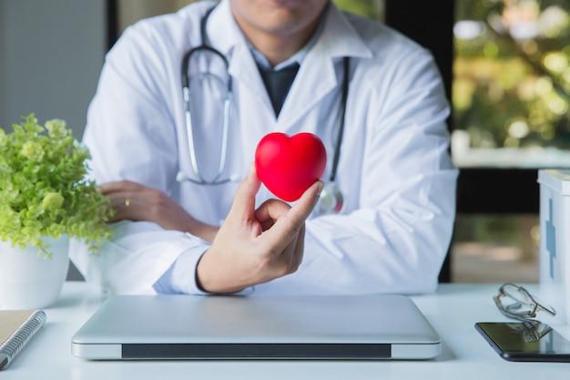 Medico con lo stetoscopio sul collo che si siede al tavolo di lavoro che tiene cuore rosso in ospedale